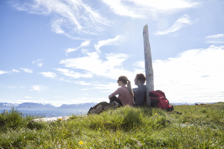 Iceland, hiking couple resting on a meadow looking at view