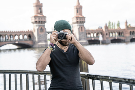 Germany, Berlin, man standing in front of Oberbaum taking pictures from viewer