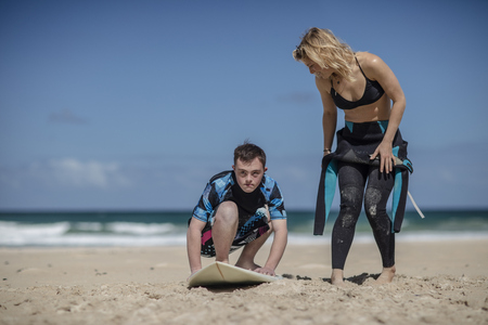 Teenage boy with down syndrome having surf lessons on beach