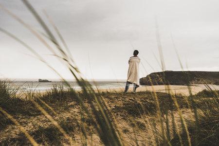 France, Bretagne, Crozon peninsula, woman standing at the coast