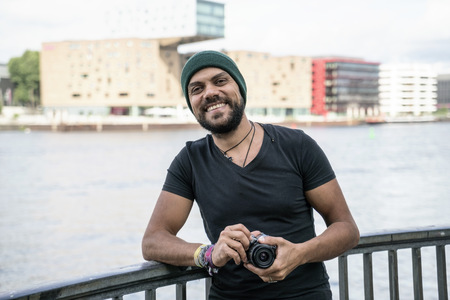 Germany, Berlin, portrait of happy man with camera