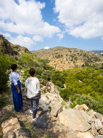 Oman, Jabal Akhdar, Women looking at the abandoned village Wadi Bani Habin LANG_EVOIMAGES