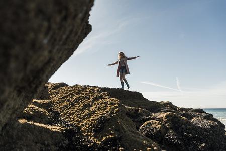 France, Crozon peninsula, teenage girl walking on rock at the coast LANG_EVOIMAGES