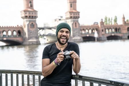 Germany, Berlin, portrait of happy man with camera standing in front of Oberbaum Bridge