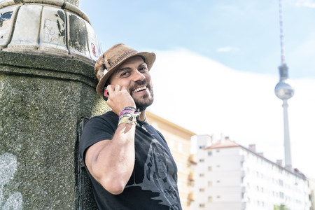 Germany, Berlin, portrait of smiling man on the phone with television tower in the background LANG_EVOIMAGES