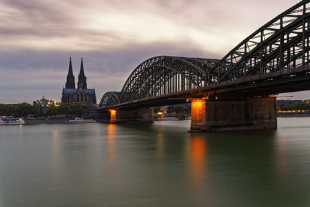 Germany, Cologne, view to Cologne Cathedral with Hohenzollern Bridge in the foreground at evening twilight