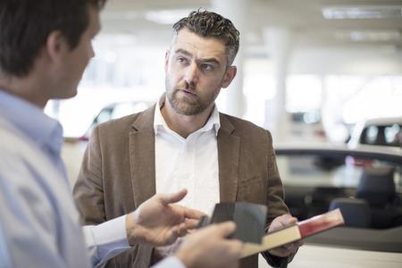 Car dealer handing over color sample to client in showroom