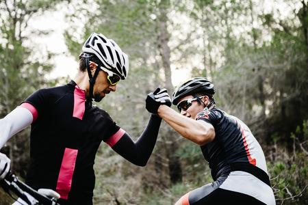 Two mountainbikers shaking hands in forest