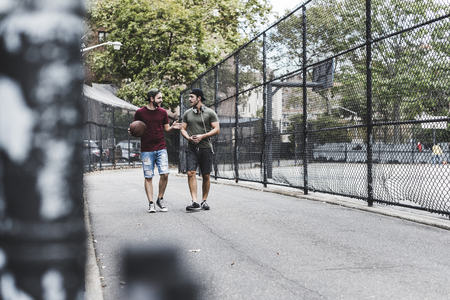 Two friends walking with basketball outdoors LANG_EVOIMAGES
