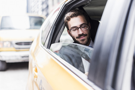 USA, New York City, smiling businessman in a taxi