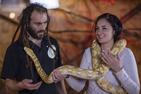 Animal attendant handing over albino python snake to woman