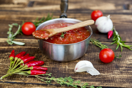 Saucepan of homemade tomato sauce and ingredients on wood