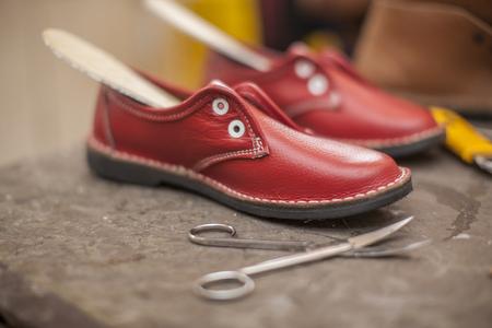 Unfinished red shoes in shoemakers workshop LANG_EVOIMAGES