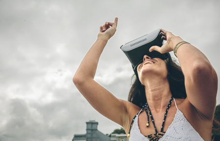 Smiling woman using Virtual Reality Glasses outdoors LANG_EVOIMAGES