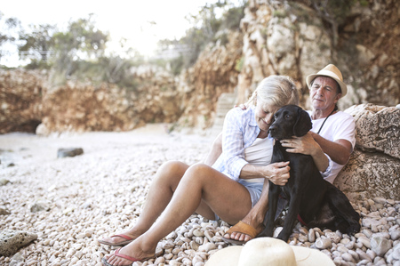 Woman cuddling dog on the beach while husband watching her