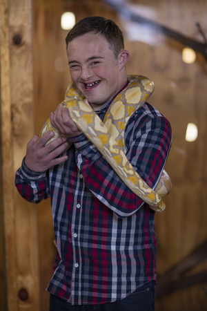 Young man with down syndrome holding albino python snake LANG_EVOIMAGES
