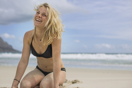 Happy young woman on the beach LANG_EVOIMAGES