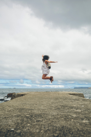 Woman on pier jumping in the air