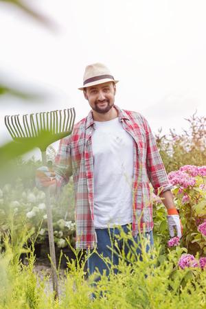 Portrait of gardener with rake