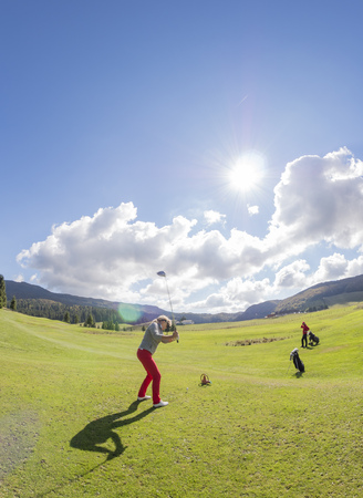 Italy, Veneto, Dolomites, senior couple on golf course