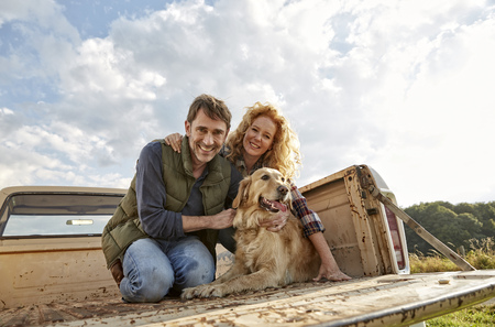 Happy couple with dog on pick up truck LANG_EVOIMAGES