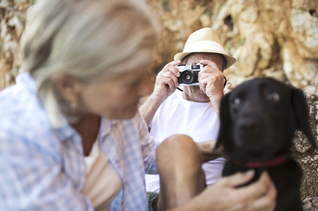 Senior man taking picture of his wife on the beach LANG_EVOIMAGES
