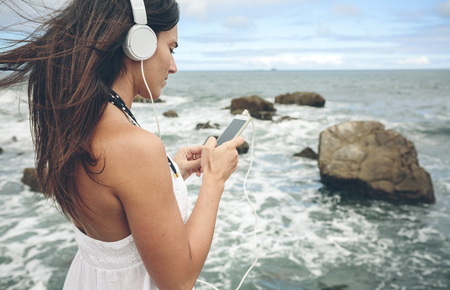 Woman listening music with headphones and smartphone in front of the sea LANG_EVOIMAGES
