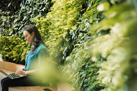 Young woman using laptop in front of green plant wall LANG_EVOIMAGES
