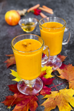 Two glasses of pumpkin smoothie and autumn leaves