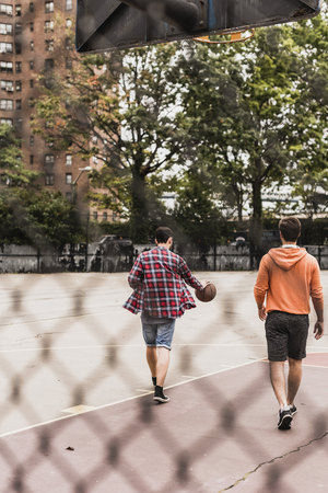Two young with basketball walking on an outdoor court