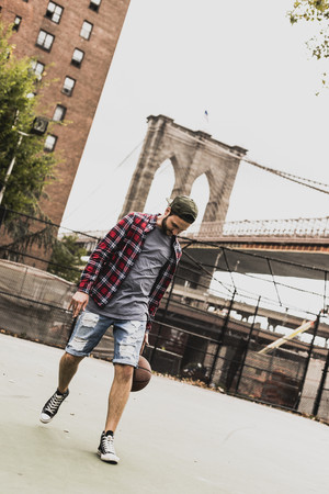 USA, New York, young man playing basketball on an outdoor court LANG_EVOIMAGES