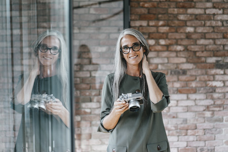 Portrait of smiling woman with long grey hair holding camera LANG_EVOIMAGES