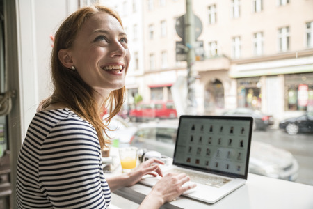 Smiling woman using laptop in a coffee shop LANG_EVOIMAGES