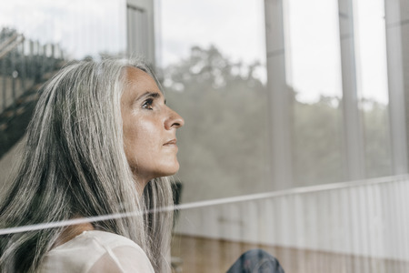 Woman with long grey hair looking out of window
