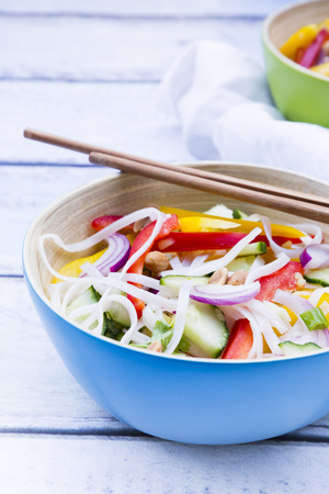 Bowl of glass noodle salad with vegetables on wood LANG_EVOIMAGES