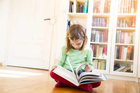Little girl sitting on the floor watching turning pages of a book