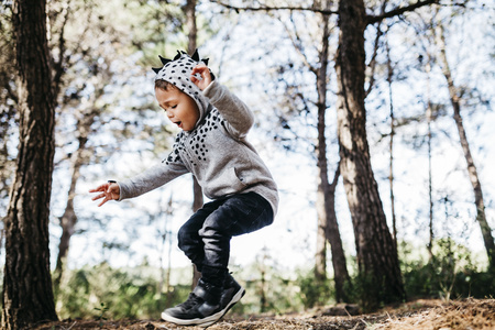 Little boy jumping in the air in the woods