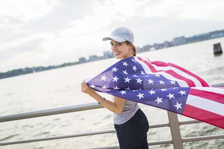 USA, Manhattan, happy woman with American flag