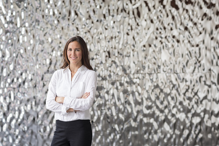 Portrait of confident businesswoman in front of rippled wall LANG_EVOIMAGES