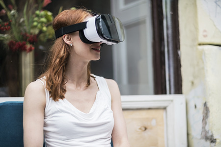 Redheaded woman wearing Virtual Reality Glasses LANG_EVOIMAGES