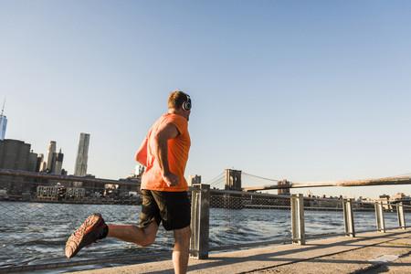 USA, Brooklyn, man jogging with headphones