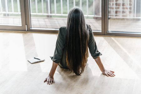 Woman sitting on the floor looking out of window