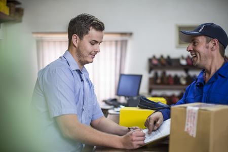 Man in warehouse signing on document for purchase LANG_EVOIMAGES