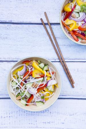 Bowls of glass noodle salad with vegetables on wood LANG_EVOIMAGES