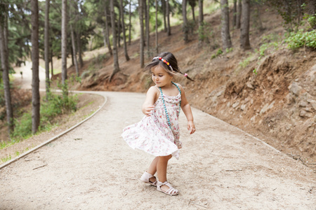 Little girl dancing on forest track