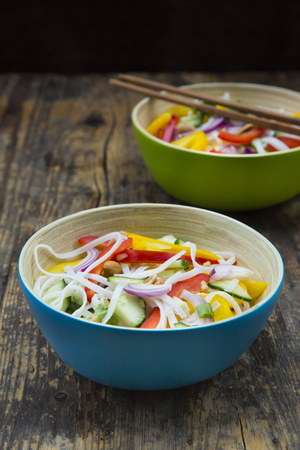 Bowls of glass noodle salad with vegetables on dark wood