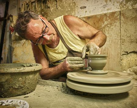 Potter in workshop working on vase LANG_EVOIMAGES