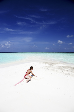Maldives, woman on beach at shallow water LANG_EVOIMAGES