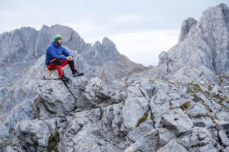 Spain, Picos de Europa, mountaineer resting on rock LANG_EVOIMAGES