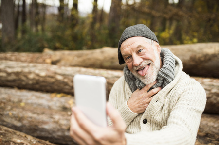 Portrait of senior man pulling funny faces while taking selfie
